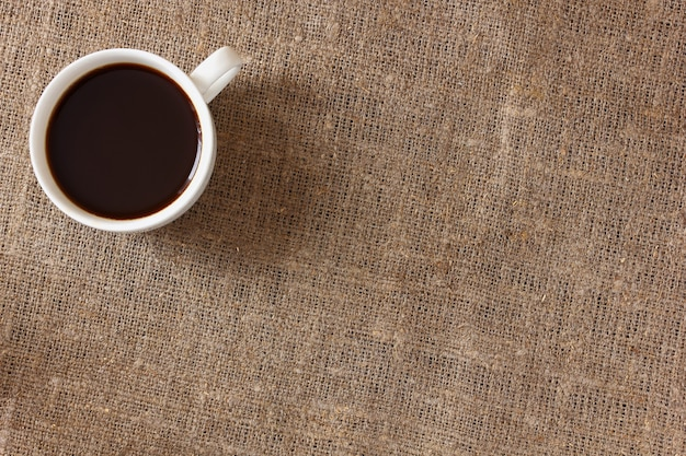 White mug with coffee on rough burlap tablecloth, top view.