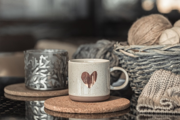 White mug with heart and wicker basket with balls of thread