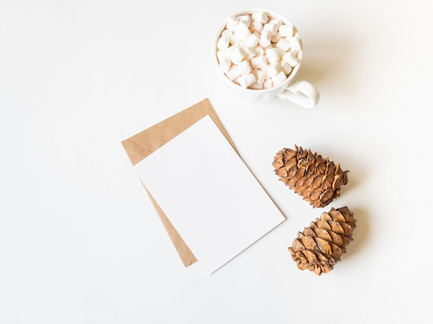 White mug with hot drink and marshmallows, paper card for letter, envelope and two cedar cones