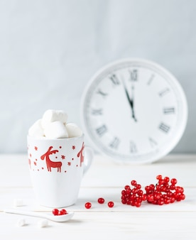 White mug with hot drink and marshmallows, red viburnum berries, jug and clock.