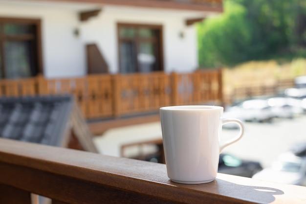 木製のテラスで温かい飲み物と白いマグカップ