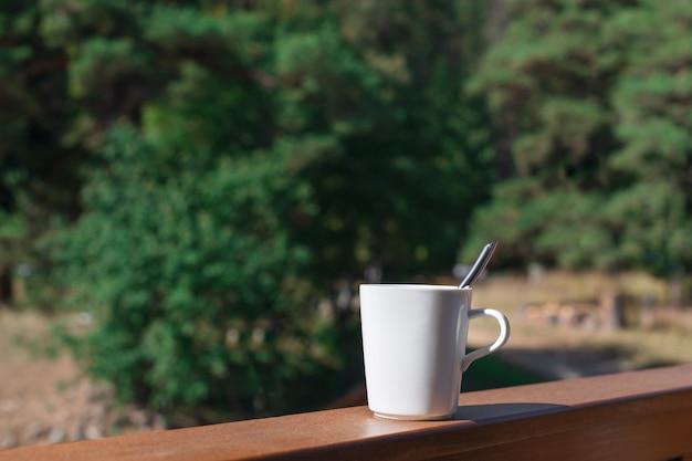 バルコニーで温かい飲み物と白いマグカップ