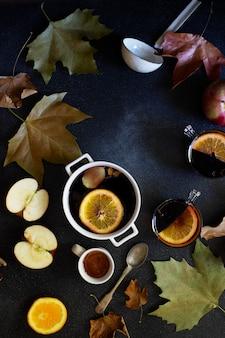グリューワインと白いマグカップ。秋と冬の暖かいアルコール飲料。紅葉、蜂蜜、リンゴ、オレンジ、ヴィンテージ料理。秋の居心地の良いムード。フラット横たわっていた、暗い背景