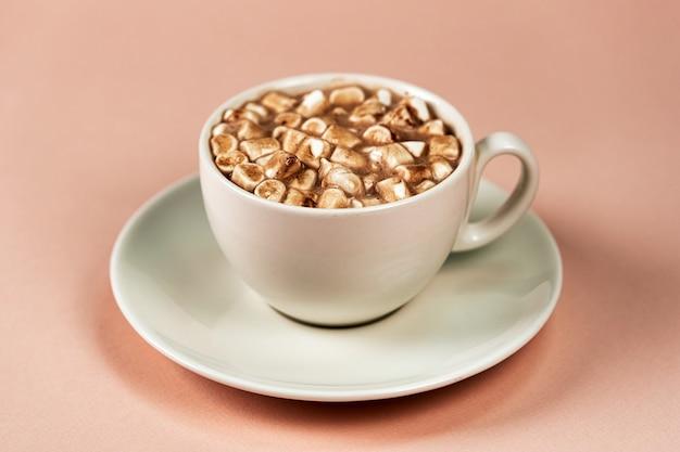 受け皿付きの白いマグカップ。マシュマロ入りコーヒー。ピンクの背景のクローズアップ