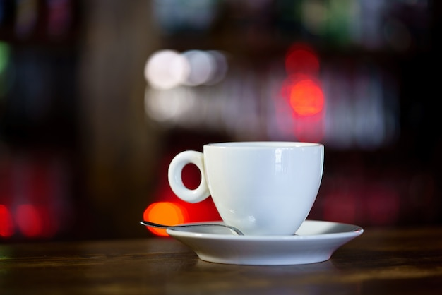 A white mug with a saucer and a spoon is on wooden table in a restaurant.