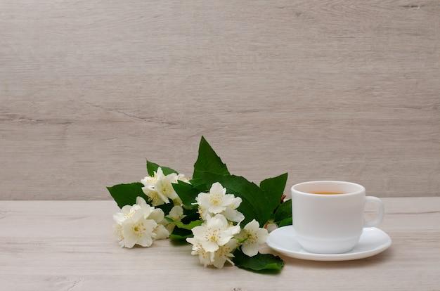 White mug with tea, a branch of jasmine on the wood