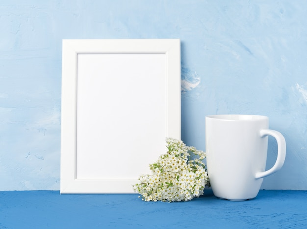 White mug with tea or coffee, frame, flower bouquet on blue table opposite blue wall.