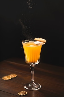 White mulled wine with a pear in a glass on a dark.