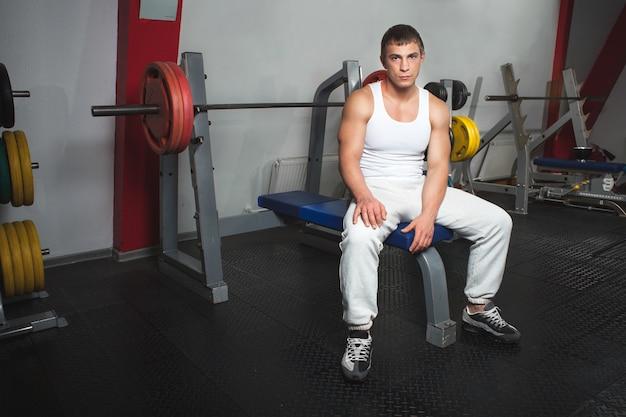 バーベルでベンチに座っているジムのインテリアで白い筋肉の男