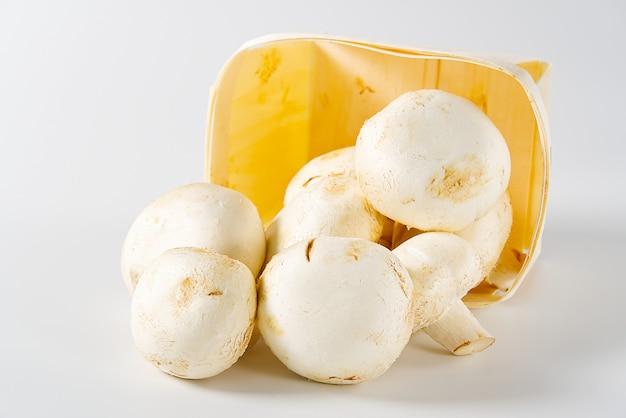 Шампиньоны белые грибы в деревянную корзину на светлом фоне.