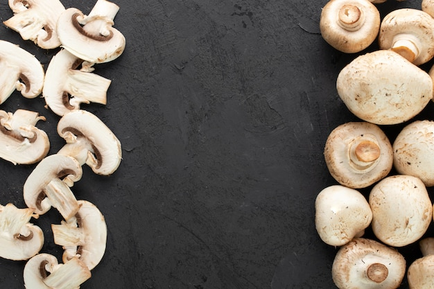 White mushrooms fresh sliced and ripe champignons on dark background