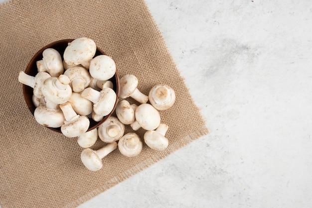 Белые грибы в деревянной чашке на куске мешковины.