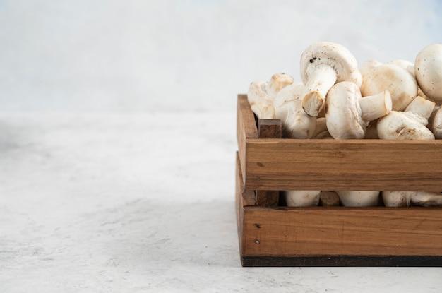 Белые грибы внутри деревянного подноса на мраморном столе.