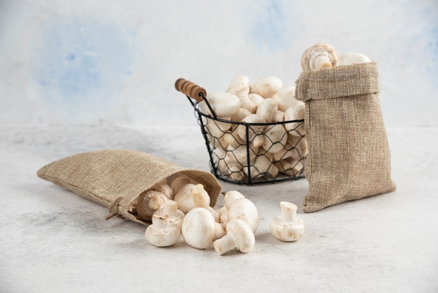 Funghi bianchi all'interno di cesti rustici e un vassoio metallico.
