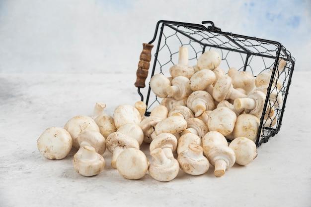 Funghi bianchi da un cesto metallico.