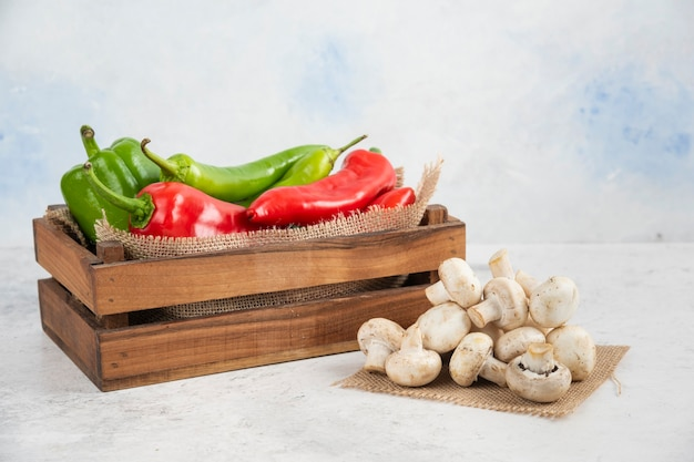 White mushrooms with red and green chili peppers in a wooden tray.