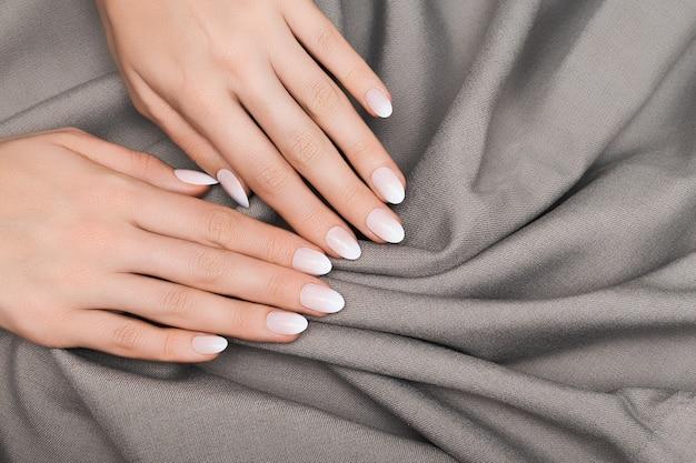 Белый лак маникюр серая тканевая поверхность.