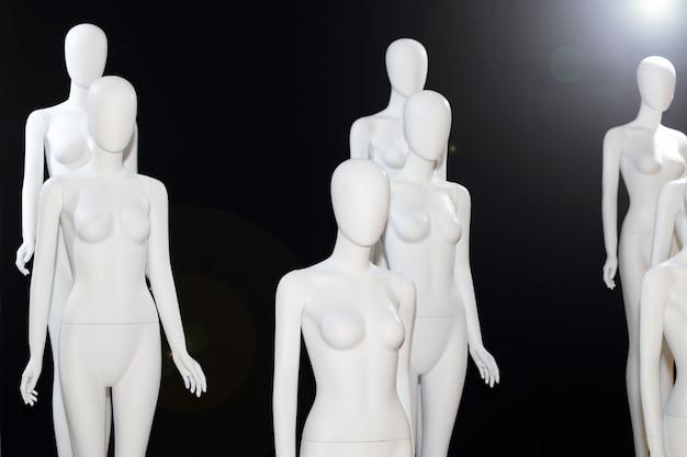 White naked mannequin over black background