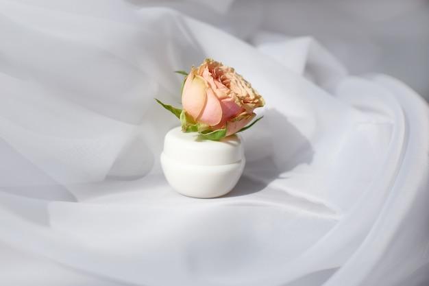 Белая баночка натуральной косметики для крема для лица с нежной розой на белой ткани. вид сбоку