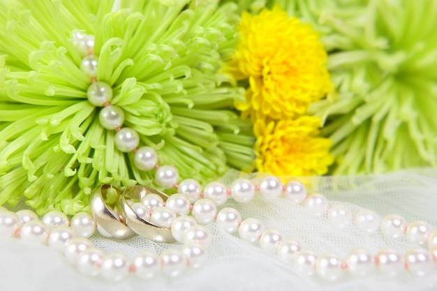 Белое колье из жемчуга, обручальные кольца и букет хризантем на белой вуали