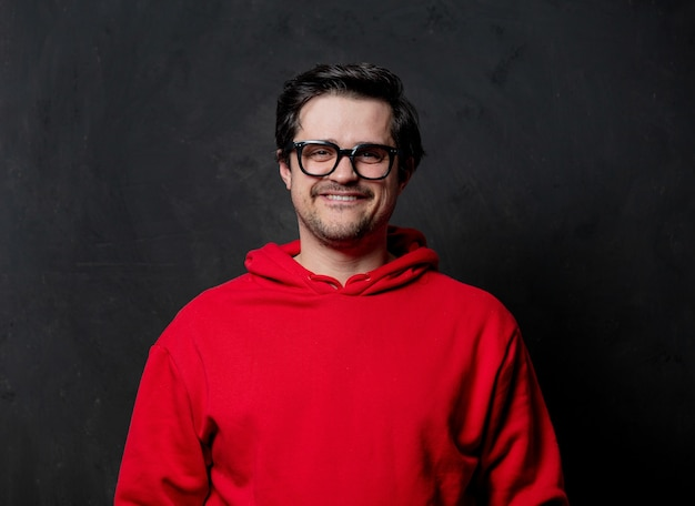 White nerd guy in red sweatshirt on dark wall