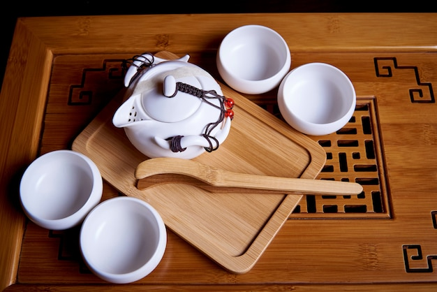White new tea set for tea ceremony on a wooden board.