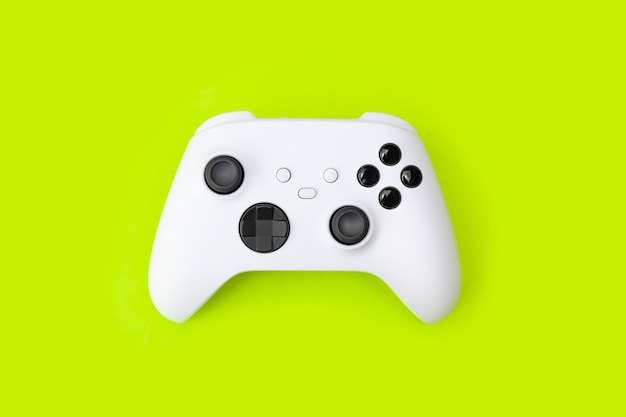 Белый игровой контроллер следующего поколения на зеленом фоне.