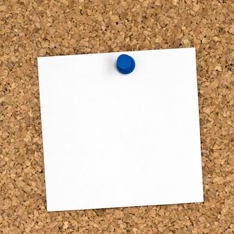 コルクボードに固定された白いノート