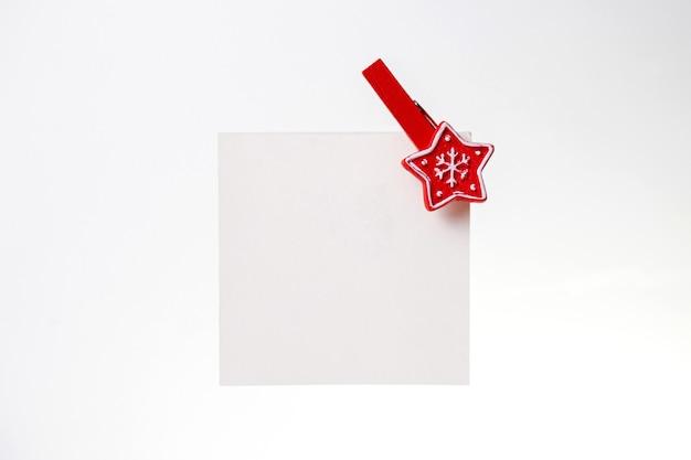 Белая записка с красной рождественской прищепкой. копировать пространство