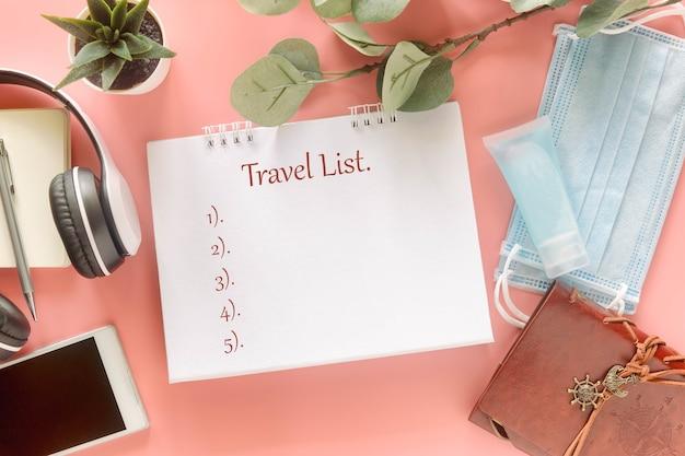 Белая записка со словом «список путешествий» с канцелярскими принадлежностями, смартфоном, наушниками, медицинскими масками и дезинфицирующим средством для рук. концепция представления списка путешественников во время новой нормальной пандемии коронавируса covid-19