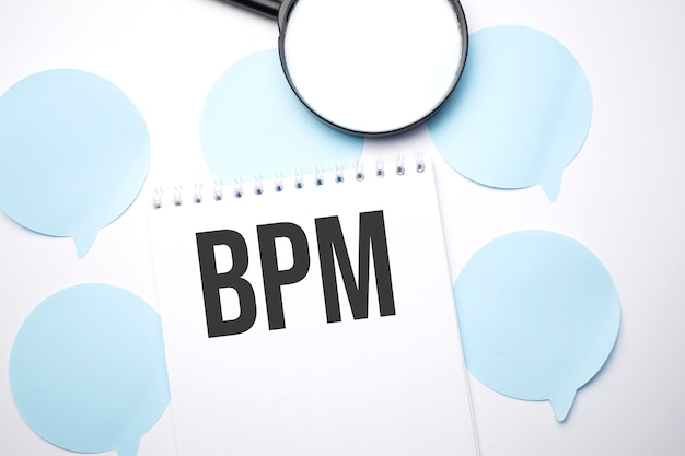 白いスピーチバブルの白いメモ帳と拡大鏡。テキストbpm。ビジネスコンセプト