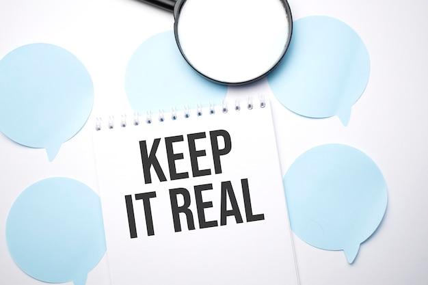 白いスピーチバブルの白いメモ帳と拡大鏡。テキストはそれを現実に保ちます。ビジネスコンセプト