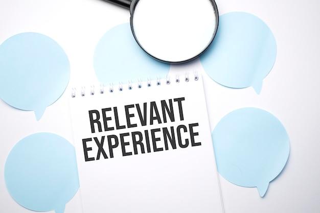 白いスピーチバブルの白いメモ帳と拡大鏡。関連する経験をテキストで伝えます。ビジネスコンセプト
