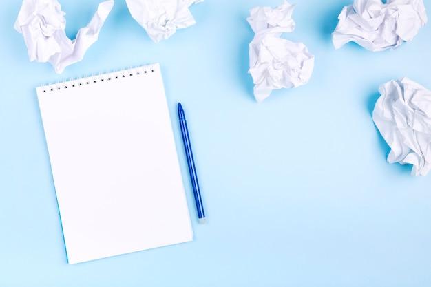화이트 노트와 구겨진 된 종이 주위 파란색 배경에 펜. 나쁜 아이디어를 버리고 계획을 세우기 시작하는 개념.