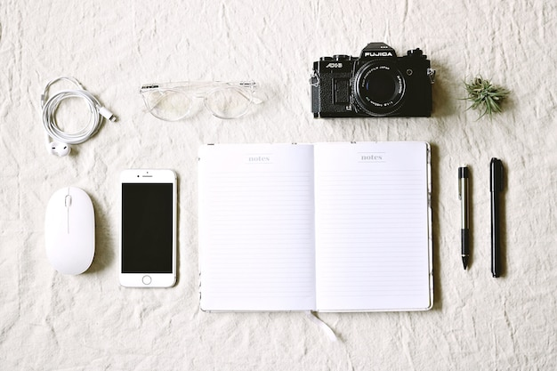 White notebook beside pens and phone and camera