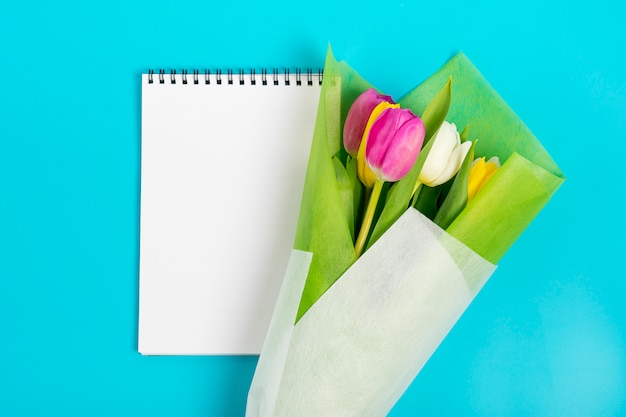 White notebook and colored tulips on a blue background flat lay