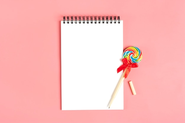 White notebook for notes, pen - lollipop on pink background flat lay