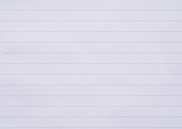 白いノートの紙のラインは背景をクローズアップ