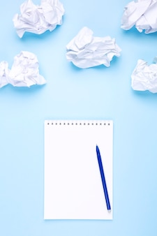 White notebook and pen on blue background around crumpled paper in the form of clouds. concept of drawing up wish list and dreams