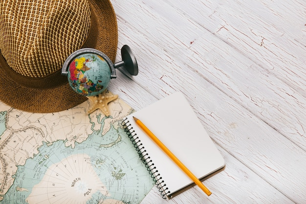 White notebook, smartphone, seastar, globe and hat lie on yellow map