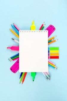 White notebook surrounded by various school office and painting supplies on blue background. back to school concept. top view. copy space