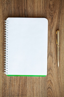 White notebook top view on wooden table.