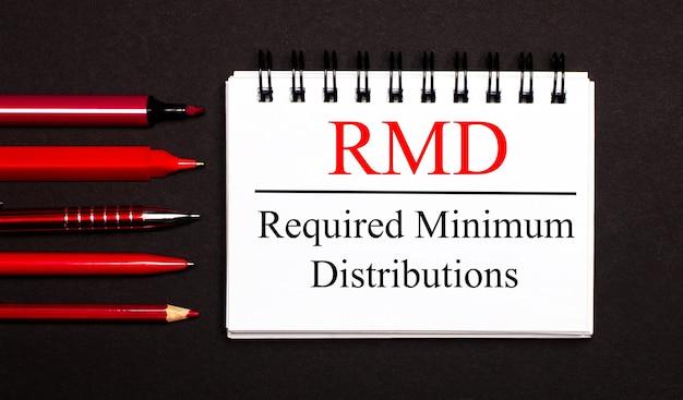 Белая записная книжка с надписью rmd required minimum distributions и красными ручками, карандашами и маркерами на черной поверхности. копировать пространство