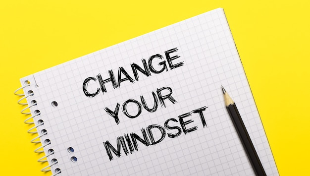 White notebook with inscription change your mindset written in black pencil on a bright yellow surface
