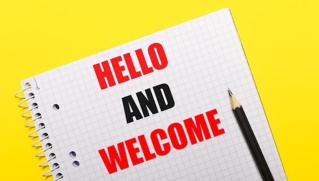 明るい黄色の背景に黒の鉛筆で書かれた「helloandwelcome」と書かれた白いノート。