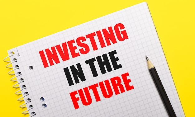 Белый блокнот с надписью «инвестиции в будущее», написанной черным карандашом на ярко-желтом фоне.