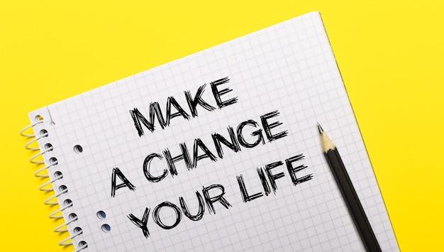 비문이있는 흰색 노트북 밝은 노란색 표면에 검은 색 연필로 작성된 인생을 바꾸십시오.