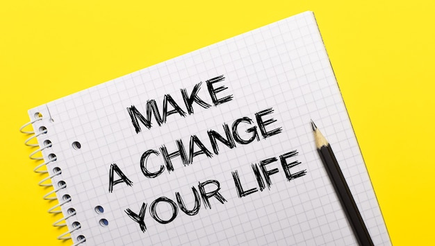White notebook with inscription make a change your life written in black pencil on a bright yellow surface