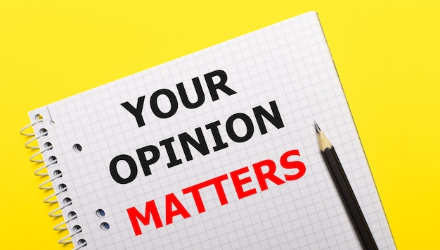 White notebook with inscription your opinion matters written in black pencil on a bright yellow background.