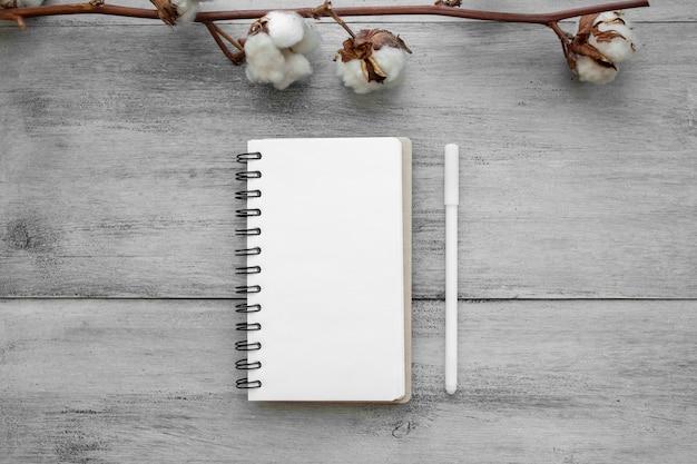 ペンと綿の軽い木製のテーブルに白いノート